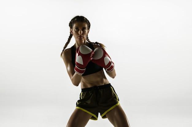 Fit blanke vrouw in sportkleding boksen geïsoleerd op een witte studio achtergrond