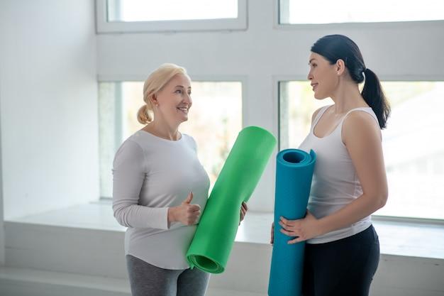 Fit blijven. blonde vrouwelijke en donkerbruine vrouwelijke het houden van yogadekens en het bespreken van iets