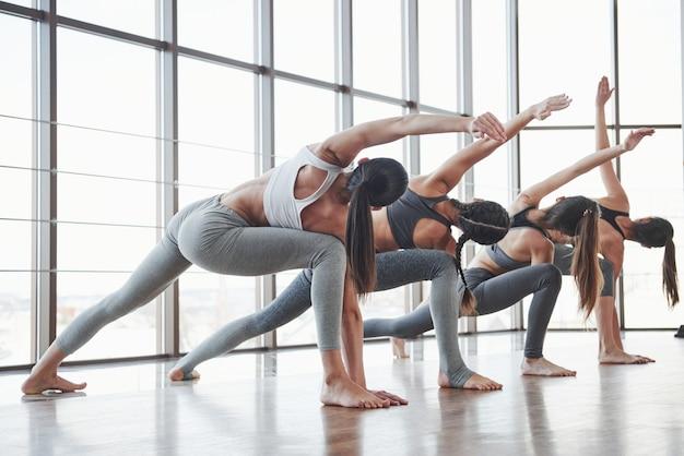 Fit blijven. groep sportieve meisjes in een ruime sportschool met grote ramen hebben training