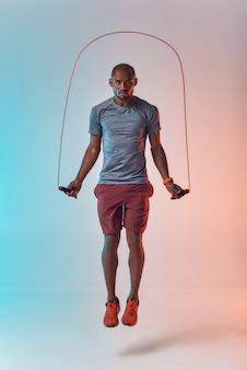 Fit blijven over de volledige lengte van een jonge afrikaanse man in sportkleding die touwtjespringt tijdens het sporten