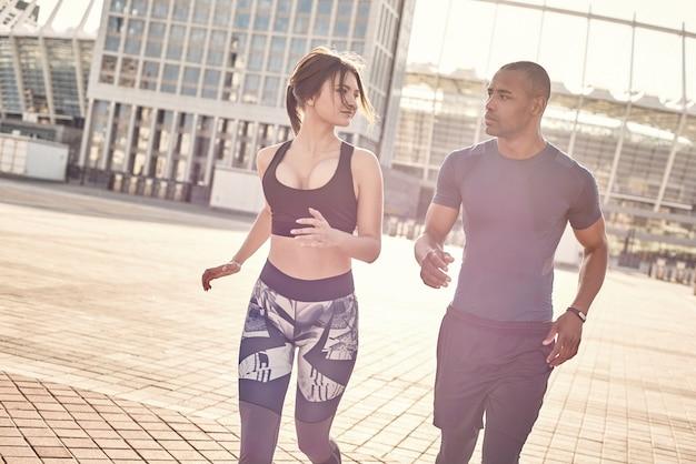 Fit blijven schattig jong interraciaal stel doet ochtendtraining en jogt samen gemeenschappelijk