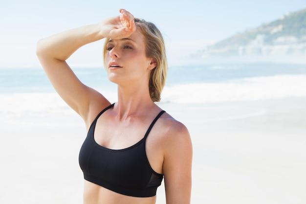 Fit blonde veegde haar voorhoofd af op het strand