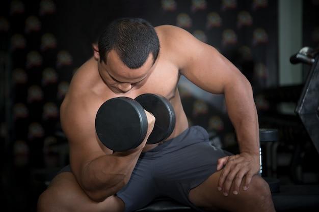 Fit bodybuilder tillen gewicht in sportschool.