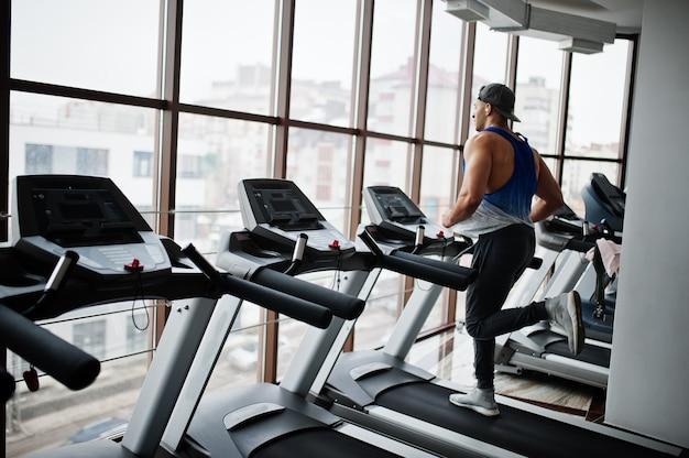 Fit en gespierd arabische man loopt op de loopband in de sportschool.