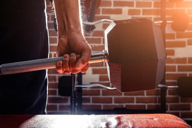 Fit en gespierde man doet biceps-trainingen met halters in sportschool, kopie ruimte.