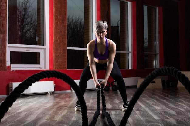 Fit en gespierde vrouw uitoefenen met vechtkabels op fitness. vrouwelijke atleet die strijdtouwtraining doen bij gymnastiek.