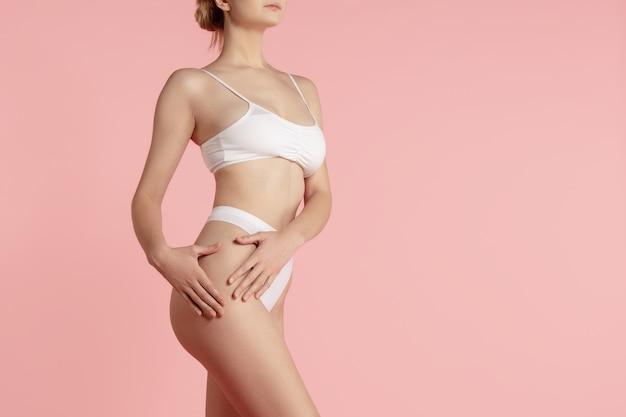 Fit en gezond. mooi vrouwelijk lichaam op roze.