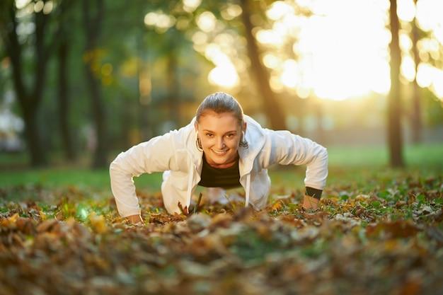 Fit en gezonde vrouw die plankpositie beoefent op frisse lucht