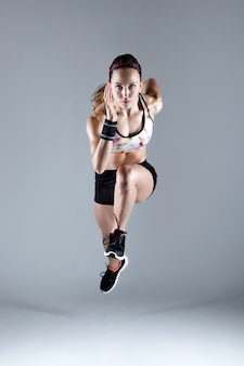 Fit en sportieve jonge vrouw die op een witte achtergrond loopt.