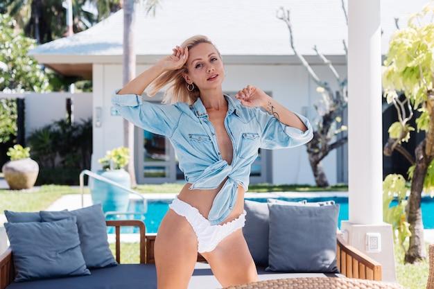 Fit europese mooie vrouw met kort blond haar in blauw denimoverhemd en wit bikinibroekje
