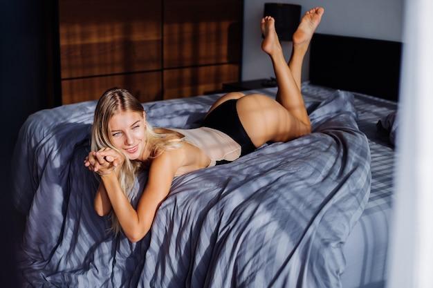 Fit europese vrouw in slaapkamer bij zonsopgang licht in beige romper in slaapkamer