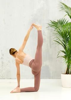 Fit flexibele vrouw die een verticale variatie van de anantasana yogapositie uitvoert met volledige beenspleet