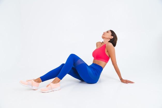 Fit gebruinde sportieve vrouw met buikspieren, fitness rondingen, het dragen van top en blauwe legging op wit