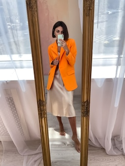 Fit gebruinde vrouw in romantische beige zijden jurk en oranje blazer thuis neemt foto selfie op telefoon in spiegel