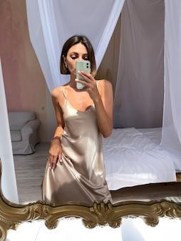 Fit gebruinde vrouw in romantische beige zijden jurk thuis neemt foto selfie op telefoon in spiegel