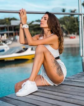 Fit gelooide brunette getatoeëerde vrouw in lichtblauwe korte broek en witte montage top zit op houten pier bij zonsondergang licht