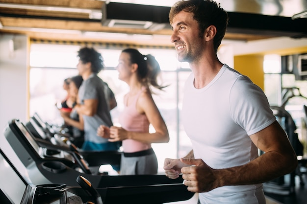 Fit gelukkige mensen lopen in machine loopband bij fitness gym