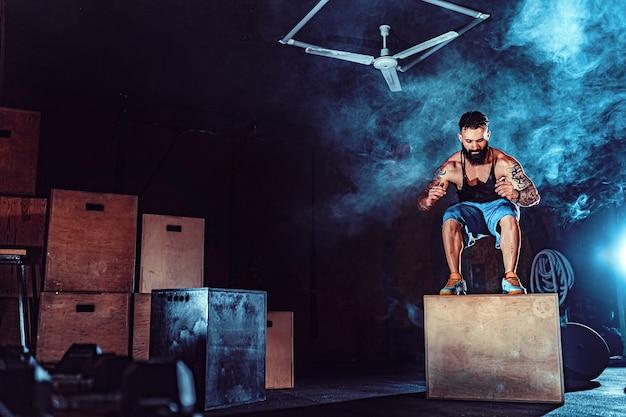 Fit getatoeëerde bebaarde man springen op een doos als onderdeel van trainingsroutine