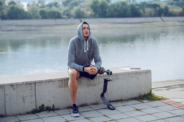Fit gezonde kaukasische gehandicapte sportman met kunstbeen en hoodie op hoofd zittend op de kade en rusten.