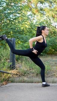 Fit gezonde vrouw in sportkleding doet oefeningen in het park met behulp van een metalen reling om haar been op te heffen voor evenwicht en controle
