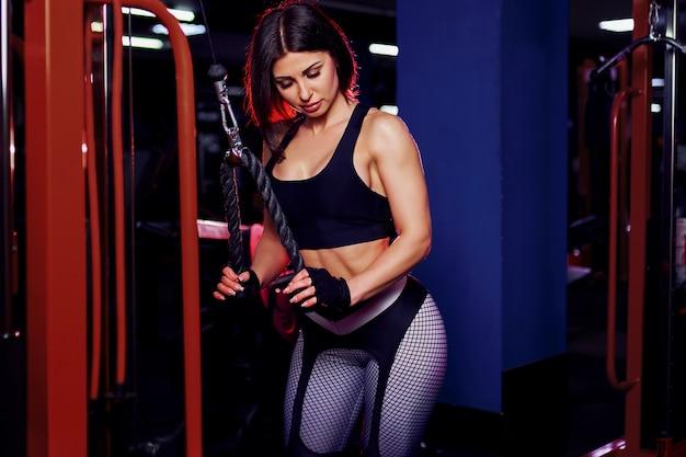 Fit goed getrainde middelbare leeftijd vrouw workout triceps tillen gewichten in de sportschool