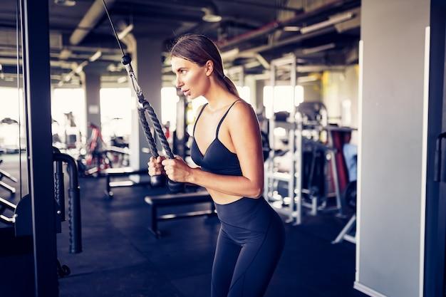 Fit goedgetrainde vrouw training triceps gewichtheffen in de sportschool. atletische sexy vrouw die oefening doet die machine in gymnastiek gebruikt - zijaanzicht.