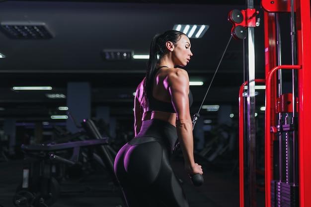 Fit goedgetrainde vrouw training triceps gewichtheffen in de sportschool. atletische sexy vrouw die oefening doet die machine in gymnastiek gebruikt