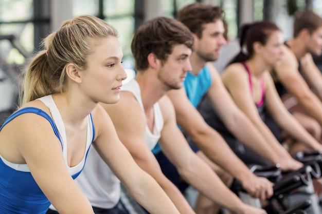 Fit groep mensen met behulp van hometrainer samen in de sportschool