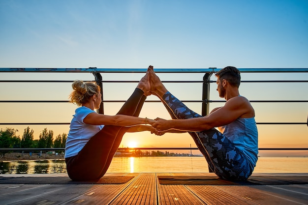 Fit jong koppel doen acro yoga op pier aan zee gezonde levensstijl mensen buitensport activiteit...