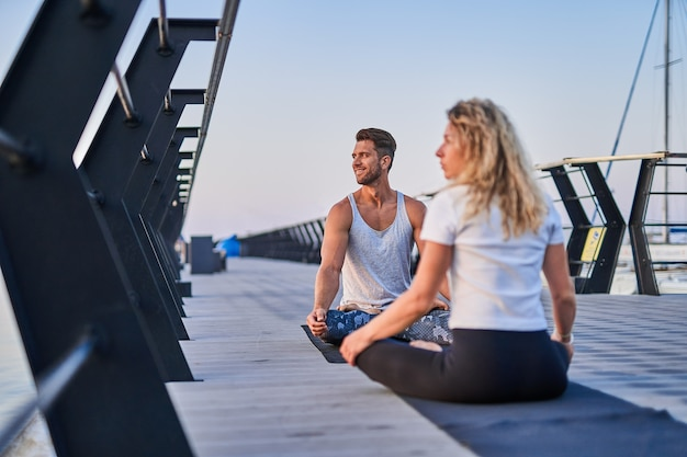 Fit jong stel doet yoga lotus pose gezonde levensstijl mensen buitensport activiteit op familie vac...