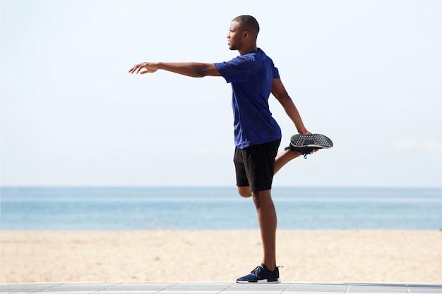 Fit jonge afrikaanse man warming-up oefening op het strand te doen