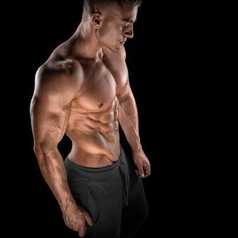 Fit jonge bodybuilder fitness mannelijk model poseren