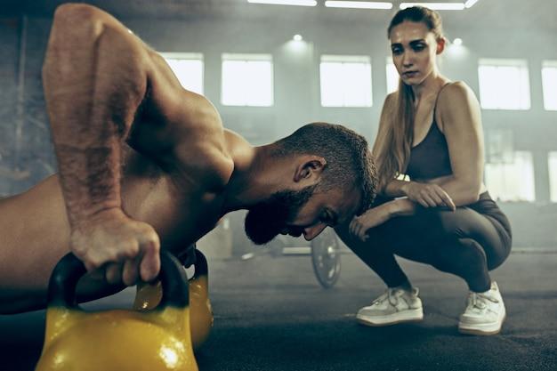 Fit jonge man tillen halters uit te werken in een sportschool