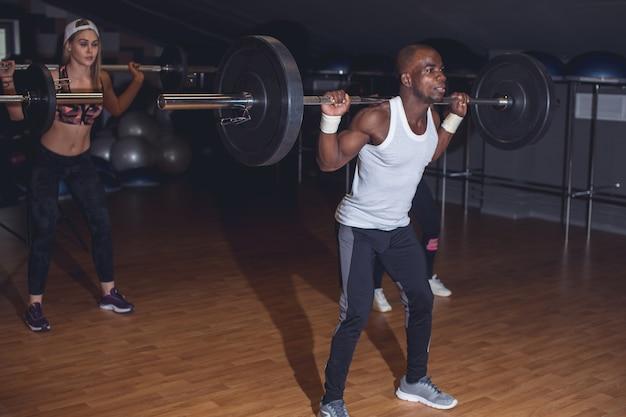 Fit jonge mensen die halters over hun hoofd tillen en er gefocust uitzien, terwijl ze in een sportschool trainen met andere mensen