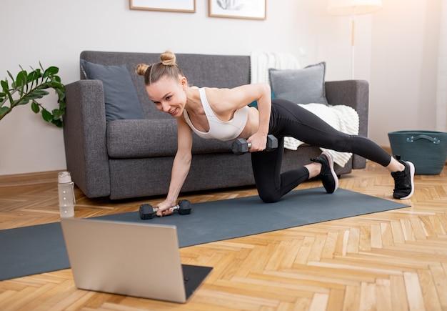 Fit jonge sportvrouw doen oefening met halters en kijken naar video op laptop tijdens online training thuis