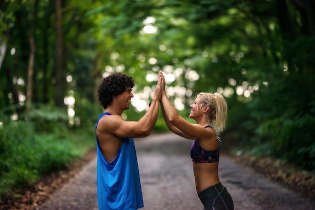 Fit jonge sterke paar geven high five aan elkaar. permanent op de atletiekbaan in een park.