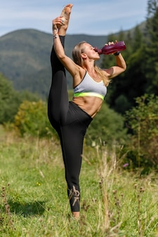 Fit jonge vrouw benen strekken en camera kijken. blanke vrouw die 's ochtends in het park traint. drinkwater. yoga en stretching, been strekken omhoog, verticaal touw