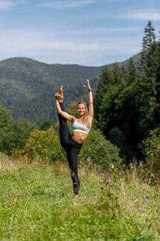 Fit jonge vrouw benen strekken en camera kijken. blanke vrouw die 's ochtends in het park traint. yoga en stretching, been strekken omhoog, verticaal touw