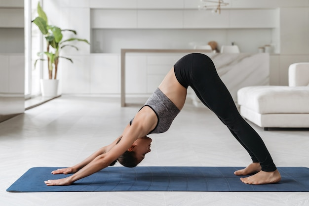 Fit jonge vrouw die thuis yoga beoefent, een naar beneden gerichte hond of adho mukha svanasana pose doet