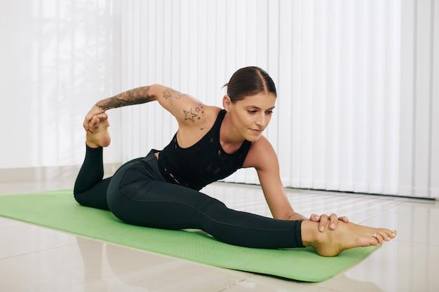 Fit jonge vrouw die zijsplitten doet en naar voren buigt naar haar rechterbeen