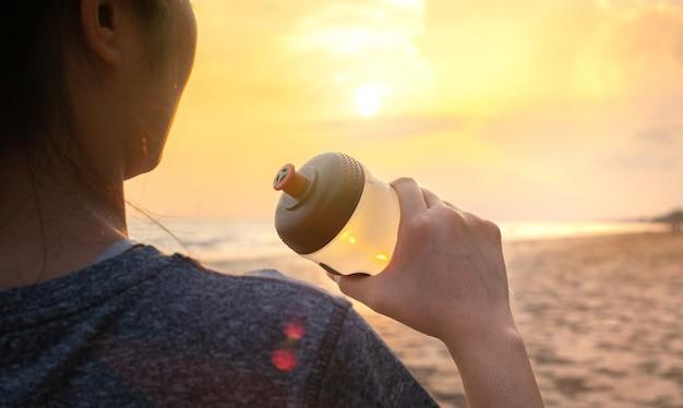Fit jonge vrouw die zoet water drinkt om te ontspannen en uit te rusten na het hardlopen, sportactiviteit uit te oefenen op het strand, de zee bij een prachtige zonsondergang