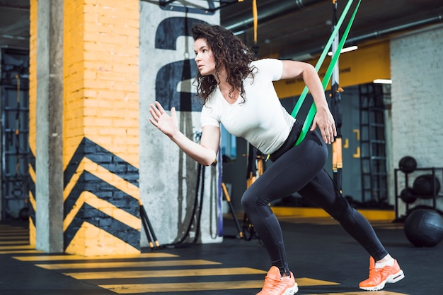 Fit jonge vrouw doen oefening in fitnessclub