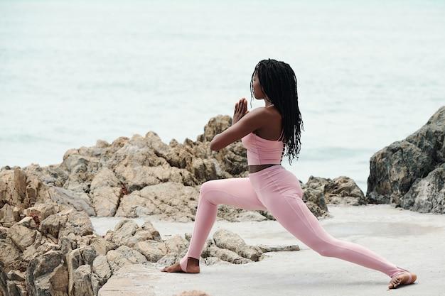 Fit jonge vrouw doet diepe lounge en hand in hand in namaste gebaar tijdens het sporten op het strand