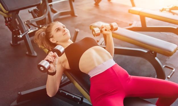 Fit jonge vrouw doet halterpers liggend op de schuine bank in de sportschool