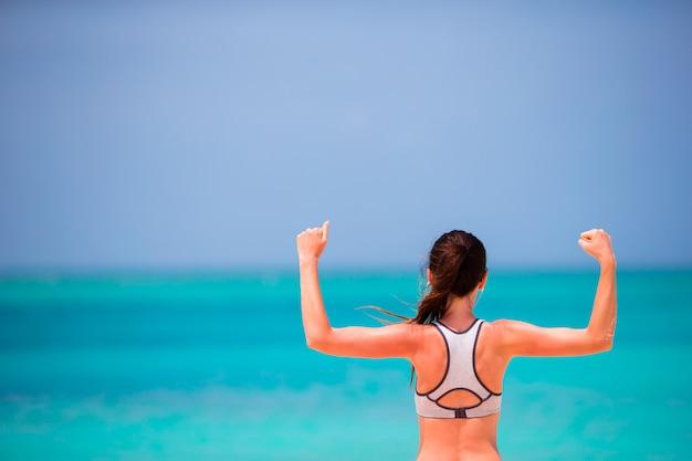 Fit jonge vrouw in haar sportkleding op het strand