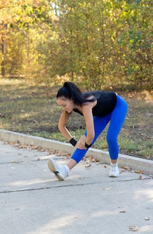 Fit jonge vrouw lenig haar spieren strekken voordat ze haar training op een geasfalteerde weg door een park begint
