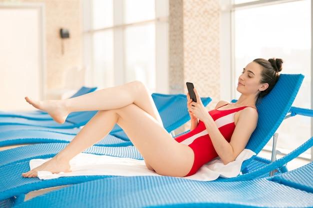 Fit jonge vrouw liggend op een van de ligstoelen na het zwemmen in het recreatiecentrum en sms'en in smartphone
