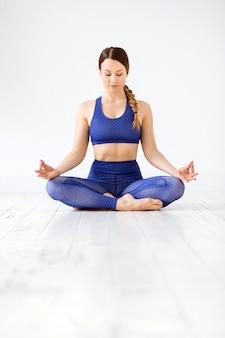 Fit jonge vrouw mediteren in yoga lotus houding op een witte vloer