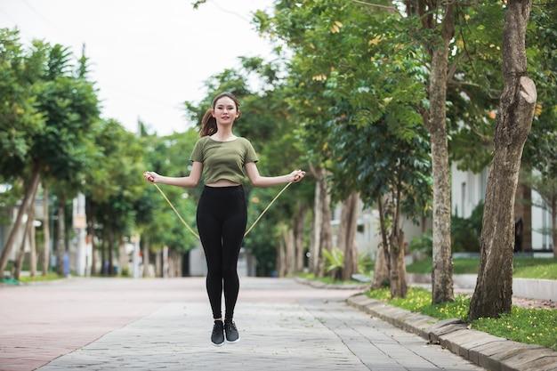 Fit jonge vrouw met springtouw in een park