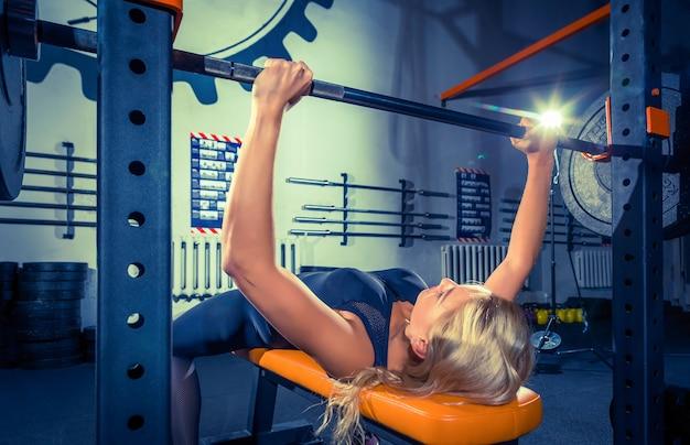 Fit jonge vrouw opheffing halters op zoek gericht trainen in een sportschool